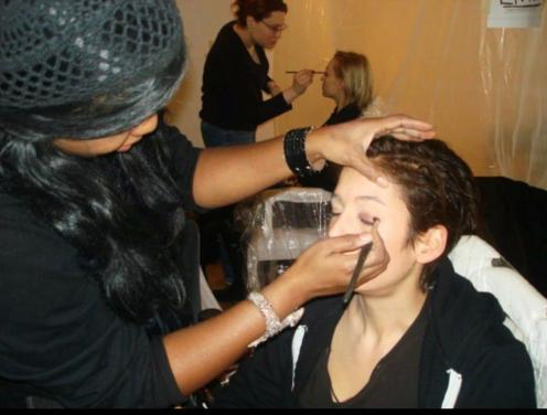 Celebrity Makeup Artist Brandy Gomez-Duplessis doing makeup backstage for NYFW